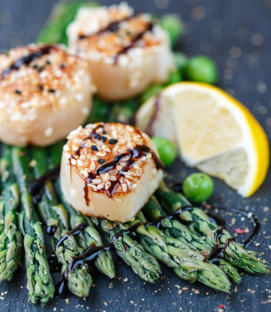 Fried scallop  with sesame seeds and balsamic sauce, asparagus, lemon and green peas on a black plate
